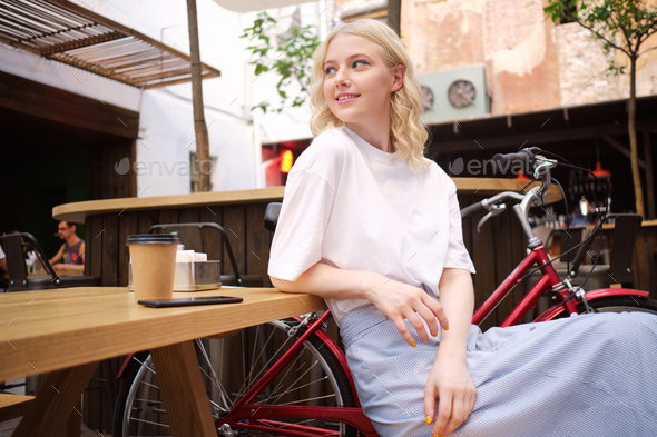 Beautiful casual blond girl happily looking away resting in courtyard of cafe - Stock Photo - Images