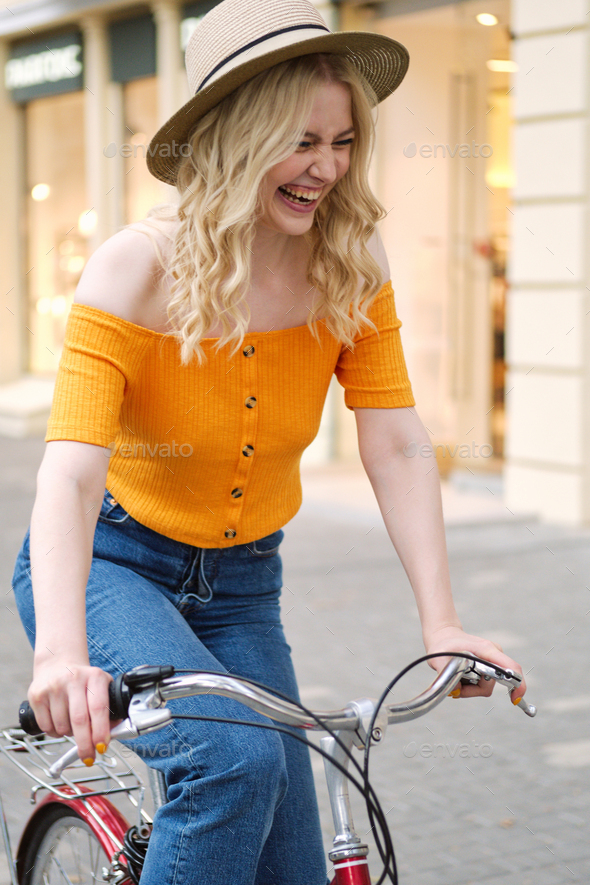 Attractive cheerful blond girl in hat joyfully riding on classic bicycle through city street - Stock Photo - Images