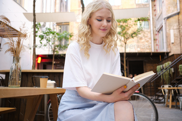 Beautiful romantic blond girl dreamily reading book in courtyard of cafe - Stock Photo - Images