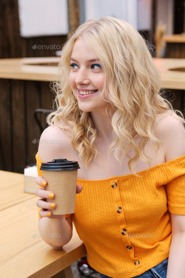 Attractive smiling casual blond girl happily looking away with coffeein hand in courtyard of cafe - Stock Photo - Images