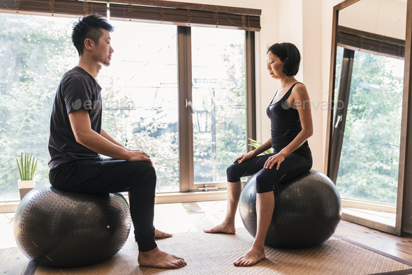 Japanese woman performing Yoga with help of personal trainer - Stock Photo - Images