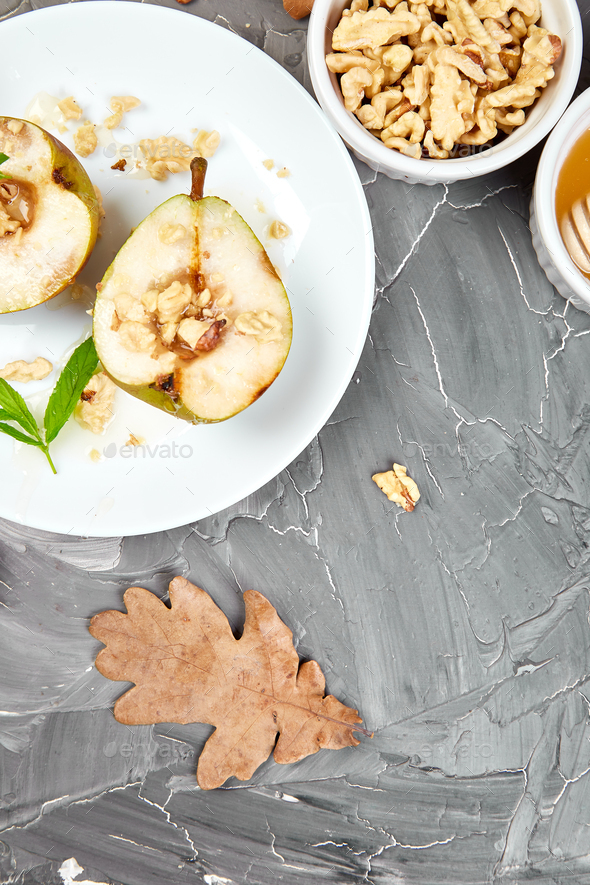 Tasty roast pears with honey and walnuts on grey background table. - Stock Photo - Images