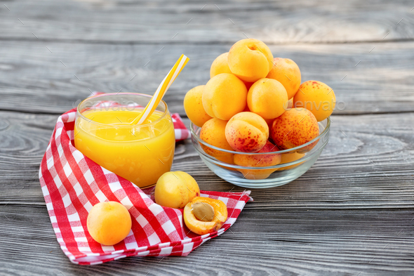 Apricot juice in glass cup with straw and apricots in bowl on wooden table - Stock Photo - Images