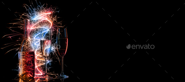 Bottle and two glasses of champagne in multi-colored sparklers on black background - Stock Photo - Images