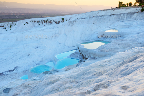 Pamukkale natural travertine terraces filled with blue water at sunset - Stock Photo - Images