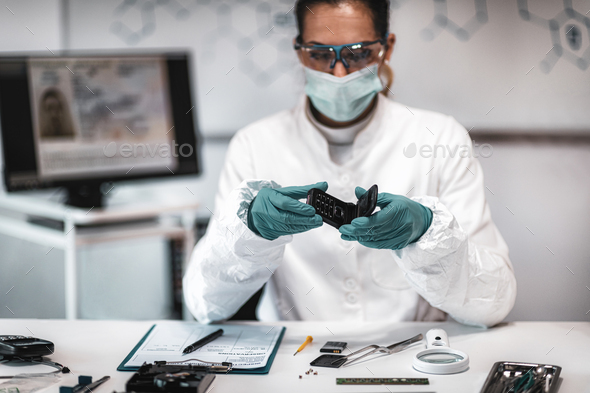 Forensics. Police Expert Examining Confiscated Mobile phone - Stock Photo - Images