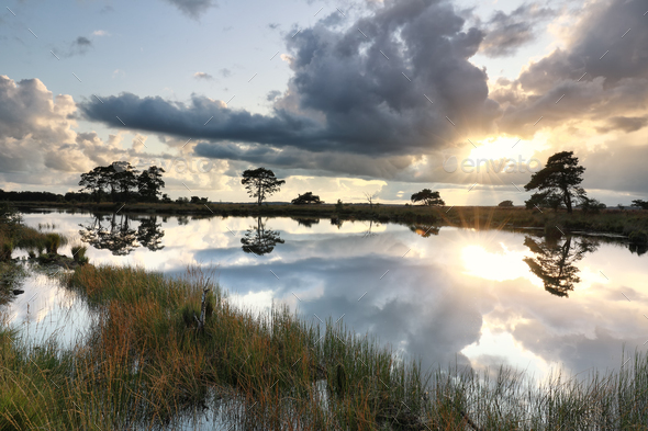 sunshine through stormy clouds over wild lake - Stock Photo - Images
