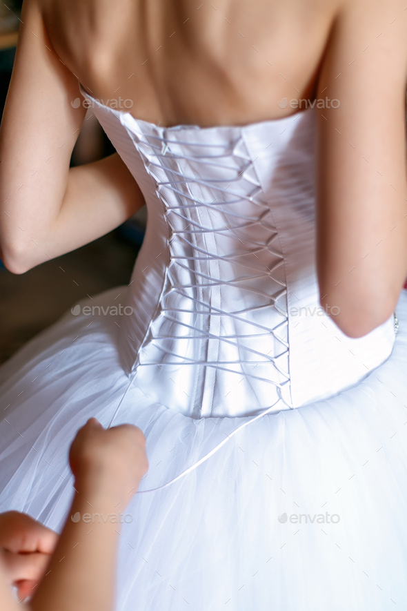 Bride is getting dressed in the room. - Stock Photo - Images