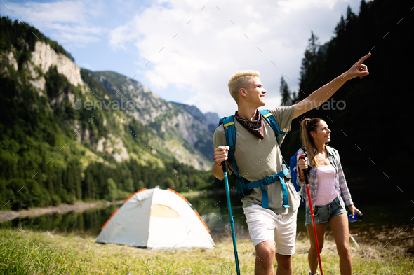 Group of happy friends with backpacks hiking together - Stock Photo - Images