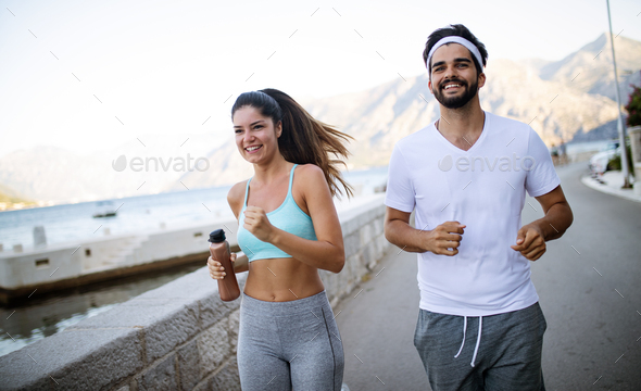 Healthy sporty lifestyle. Happy fit people friends exercising and running outdoor - Stock Photo - Images