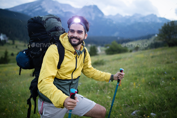 Hiker young man with backpack and trekking poles looking at the mountains in outdoor - Stock Photo - Images
