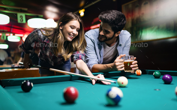 Couple dating, flirting and playing billiard in a pub - Stock Photo - Images