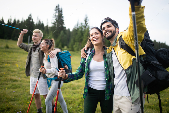 Group of hikers with backpacks and sticks walking on mountain. Friends making an excursion - Stock Photo - Images