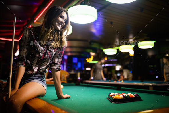 Young beautiful girl is playing billiards. Pleasant pastime, rest, entertainment - Stock Photo - Images