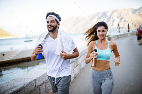 Happy young fit people couple running outdoor - Stock Photo - Images