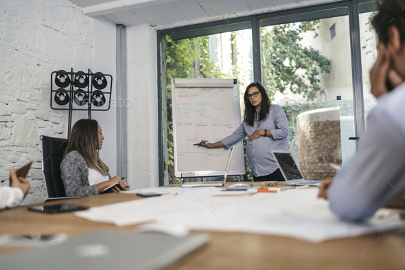 Pregnant woman working in a creative studio - Stock Photo - Images