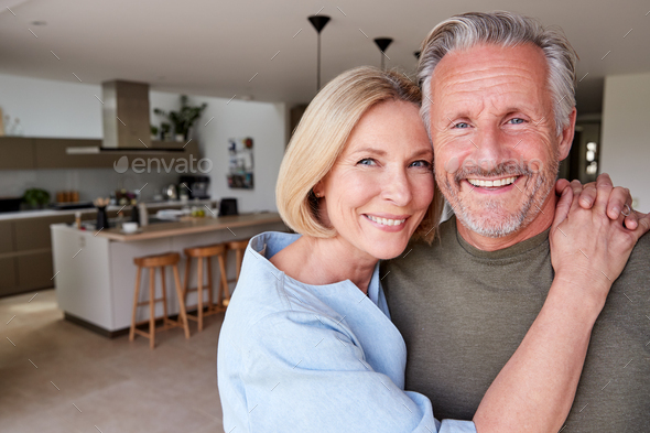 Portrait Of Smiling Senior Couple Standing At Home In Kitchen Together - Stock Photo - Images
