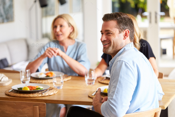 Family With Senior Mother And Adult Offspring Eating Brunch Around Table At Home Together - Stock Photo - Images
