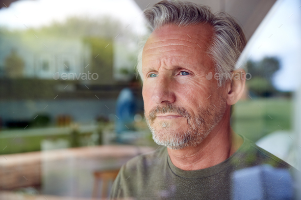 Concerned Senior Man Standing And Looking Out Of Kitchen Door Viewed Through Window - Stock Photo - Images