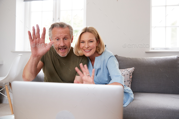 Senior Couple Sitting On Sofa At Home Making Video Call Using Laptop Computer Together - Stock Photo - Images