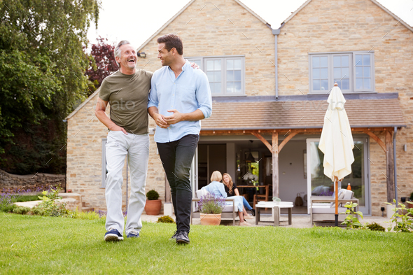 Senior Father And Adult Son Walking And Talking In Garden Together - Stock Photo - Images