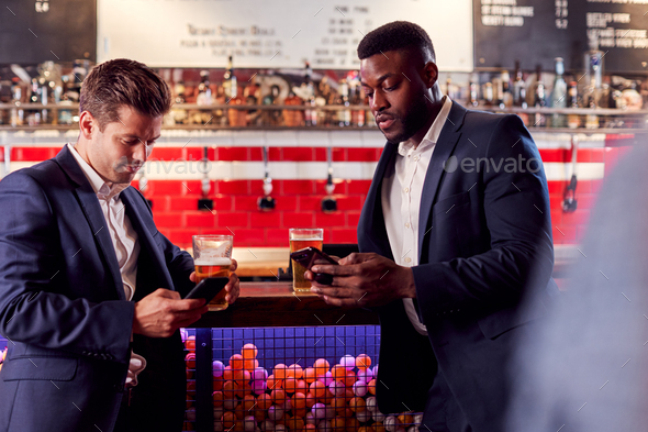 Two Businessmen Checking Mobile Phones Whilst Meeting For Drink In Bar - Stock Photo - Images