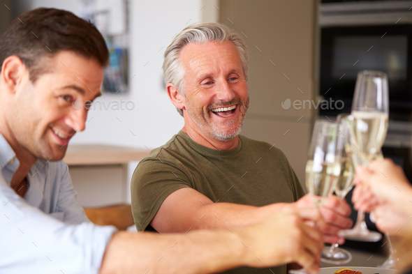 Family With Senior Parents And Adult Offspring Make A Toast Before Eating Meal Around Table At Home - Stock Photo - Images