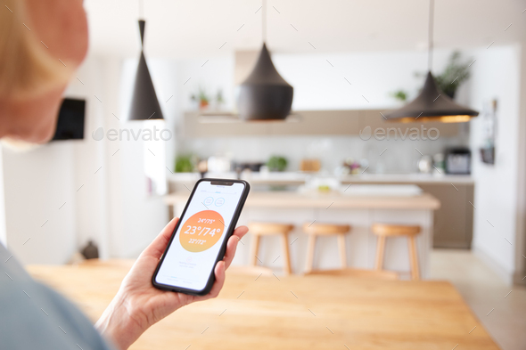 Close Up Of Woman Using App On Smart Phone To Control Central Heating Temperature In House - Stock Photo - Images