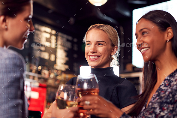 Three Women Making A Toast As They Meet For Drinks And Socialize In Bar After Work - Stock Photo - Images