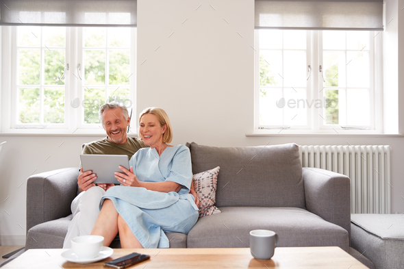 Senior Couple Sitting On Sofa In Lounge At Home Using Digital Tablet Together - Stock Photo - Images