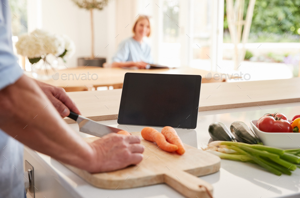 Senior Man Following Recipe On Digital Tablet As Wife Sits At Dining Room Table An Reads Magazine - Stock Photo - Images