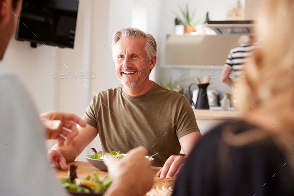 Family With Senior Parents And Adult Offspring Eating Meal Around Table At Home Together - Stock Photo - Images