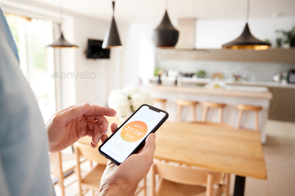 Close Up Of Man Using App On Smart Phone To Control Central Heating Temperature In House - Stock Photo - Images