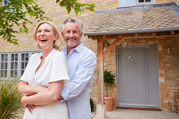 Portrait Of Senior Couple Standing Outside Front Door Of Home - Stock Photo - Images