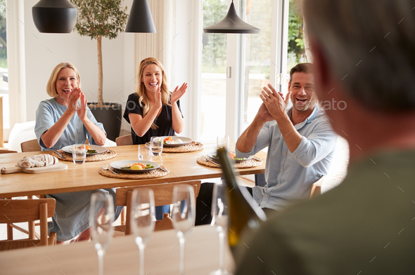 Senior Man Opens Bottle Of Champagne As Family With Adult Offspring Eat Meal Around Table At Home - Stock Photo - Images