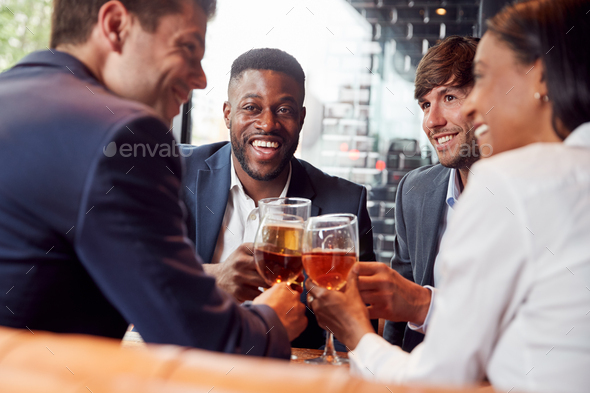 Group Of Business Colleagues Making A Toast As They Meet For Drinks And Socialize In Bar After Work - Stock Photo - Images