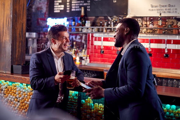 Two Businessmen Meeting For Drinks And Socializing In Bar After Work - Stock Photo - Images