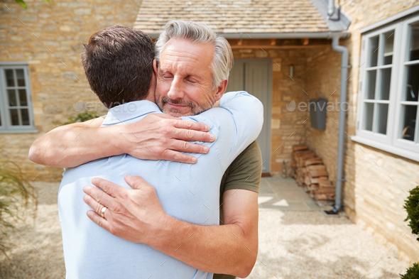 Senior Father Greets And Hugs Adult Son Outside Front Door Of House As He Visits - Stock Photo - Images