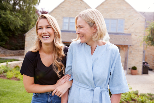 Senior Mother And Adult Daughter Walking And Talking In Garden Together - Stock Photo - Images