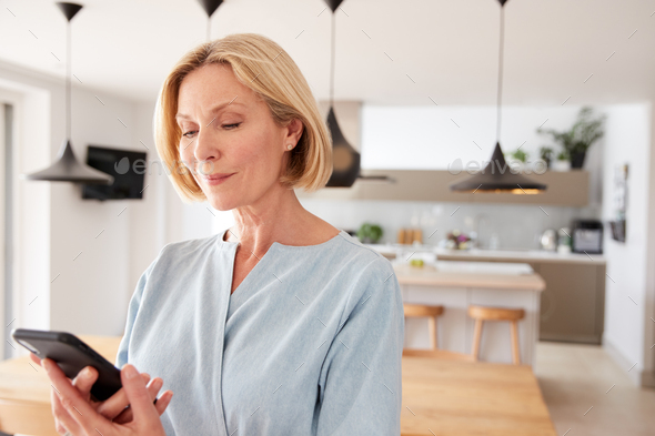 Mature Woman Using App On Mobile Phone To Control Central Heating Temperature In House - Stock Photo - Images
