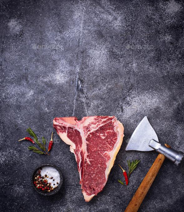 Raw T-bone steak with hatchet - Stock Photo - Images
