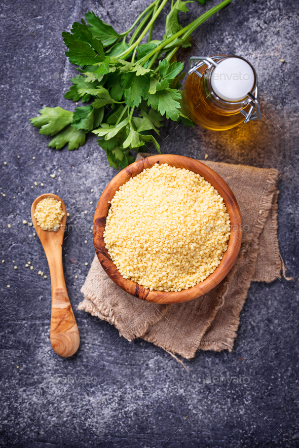 Couscous grain in wooden bowl - Stock Photo - Images