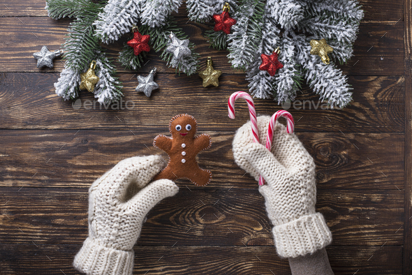 Hands in mittens holding gingerbread men - Stock Photo - Images