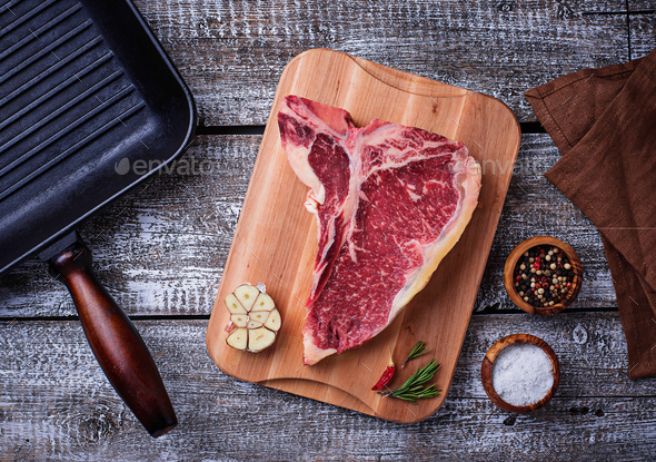 Raw T-bone steak and iron grill pan - Stock Photo - Images