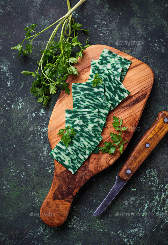 Green sliced cheese with herbs. - Stock Photo - Images