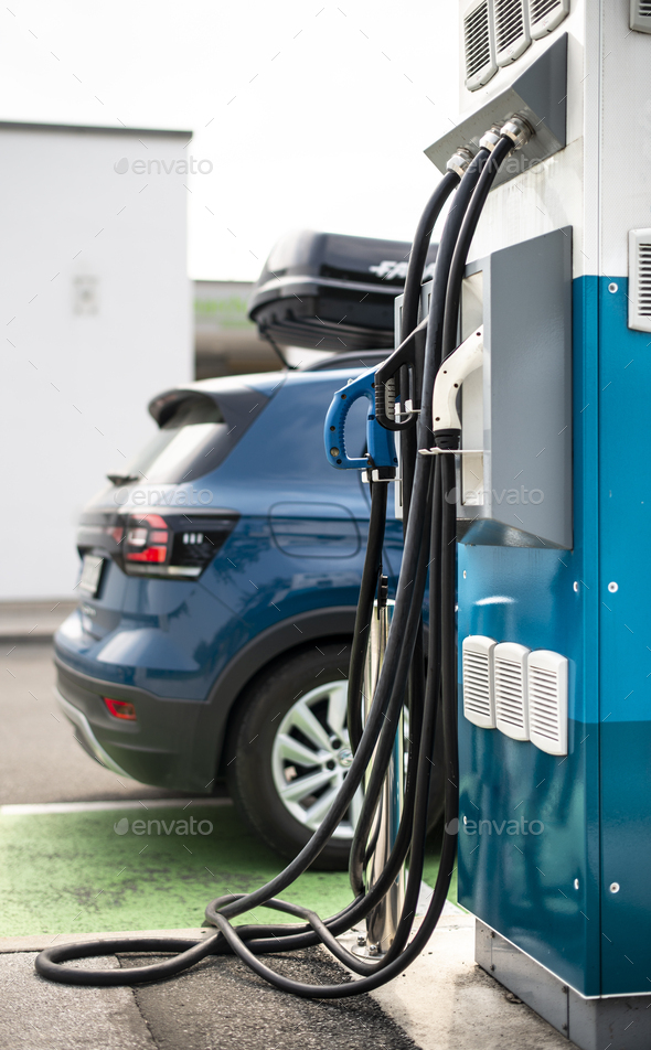 Electric car on gas station. Blue car and electric plug for char - Stock Photo - Images