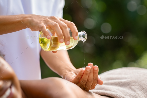 Masseuse hands pouring massage oil - Stock Photo - Images