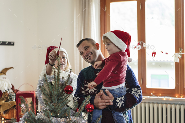happy family with a young child decorating a christmas tree at h - Stock Photo - Images