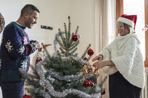 happy family with a young child decorating a christmas tree at home - Stock Photo - Images