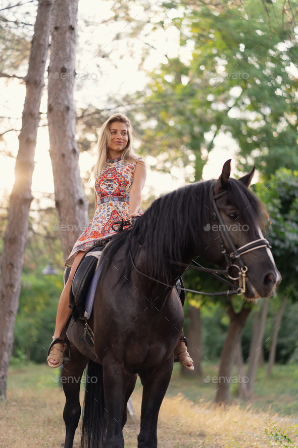 Young woman in a bright colorful dress riding a black horse - Stock Photo - Images